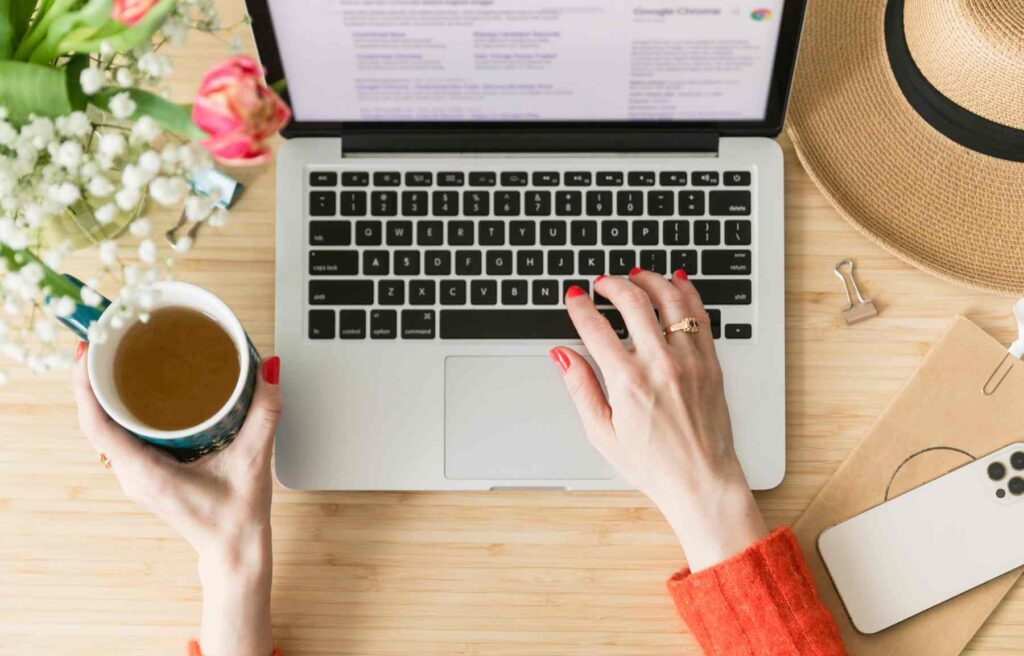 Woman typing on laptop keyboard and holding a mug of tea.