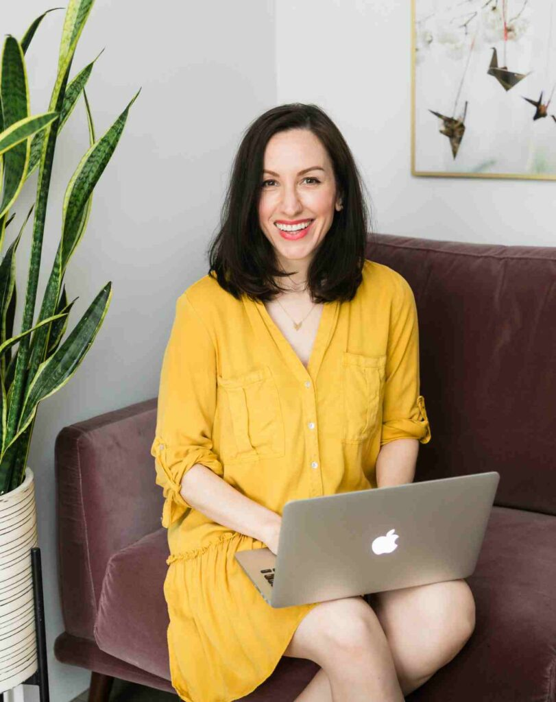 SEO coach in yellow dress typing on laptop.